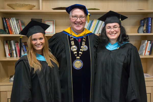 Two graduates smiling with a professor