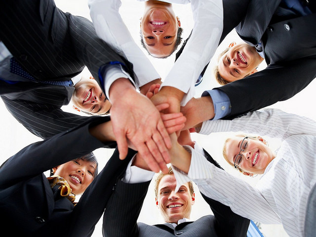 A team smiling with all their hands in