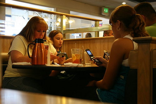 A family sitting at a table, all engrossed in their phone
